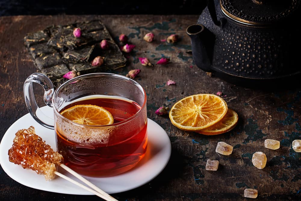 Hot Roiboos tea served in the glass cup decorated with variety of different dry tea