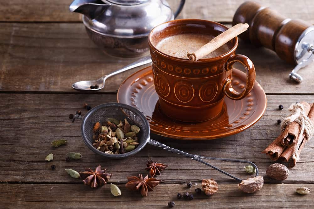 Chai tea masala and spices over rustic wooden background