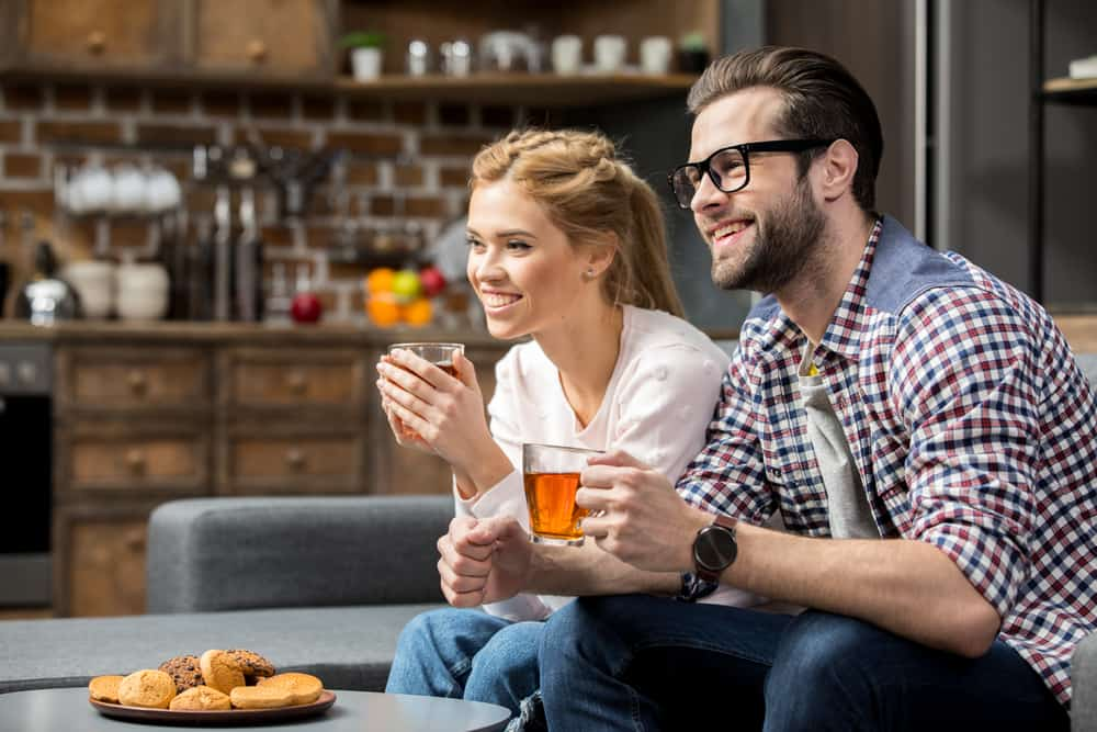 Smiling couple drinking tea with biscuits in living room