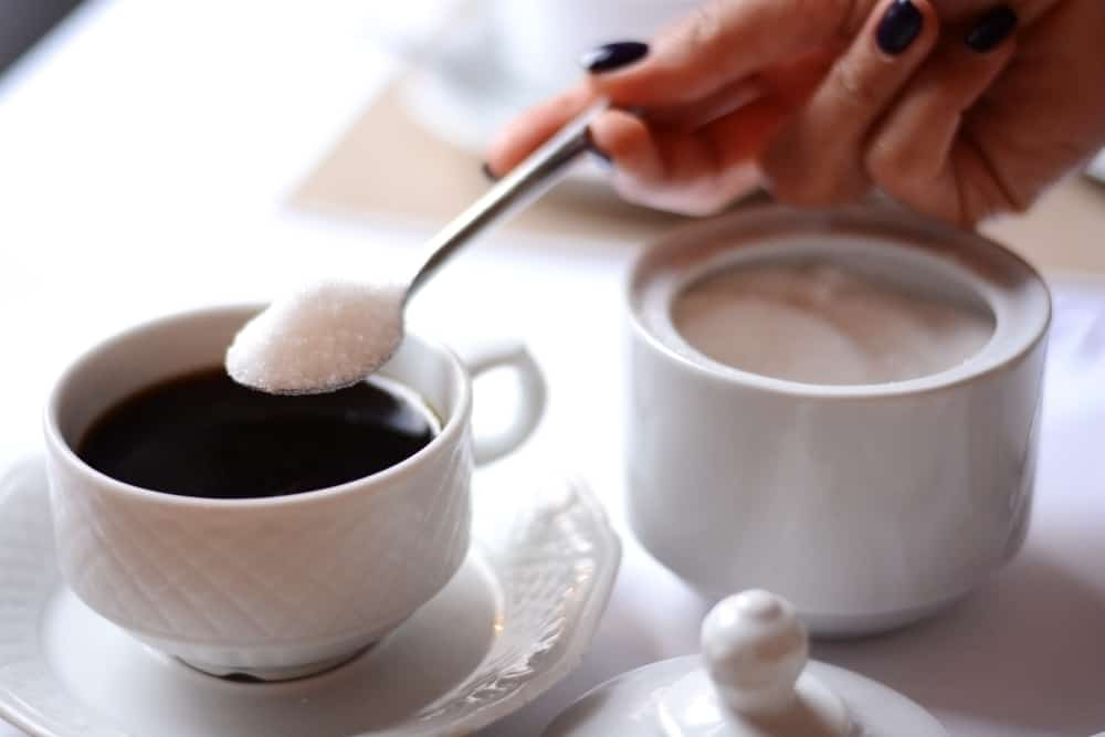 Woman hand adding a lot of sugar in a coffee from a sugar bowl
