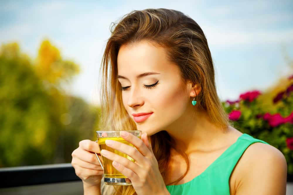 Young Woman Drinking Green Tea Outdoors. Summer Background. Shallow Depth of Field