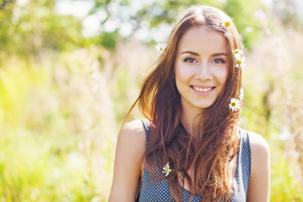cute young woman with flowers in her hair in spring