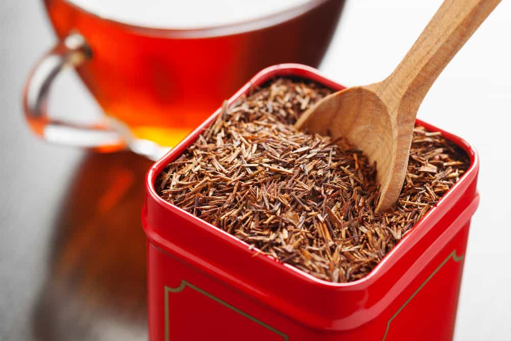 rooibos in tea tin box and wooden spoon closeup