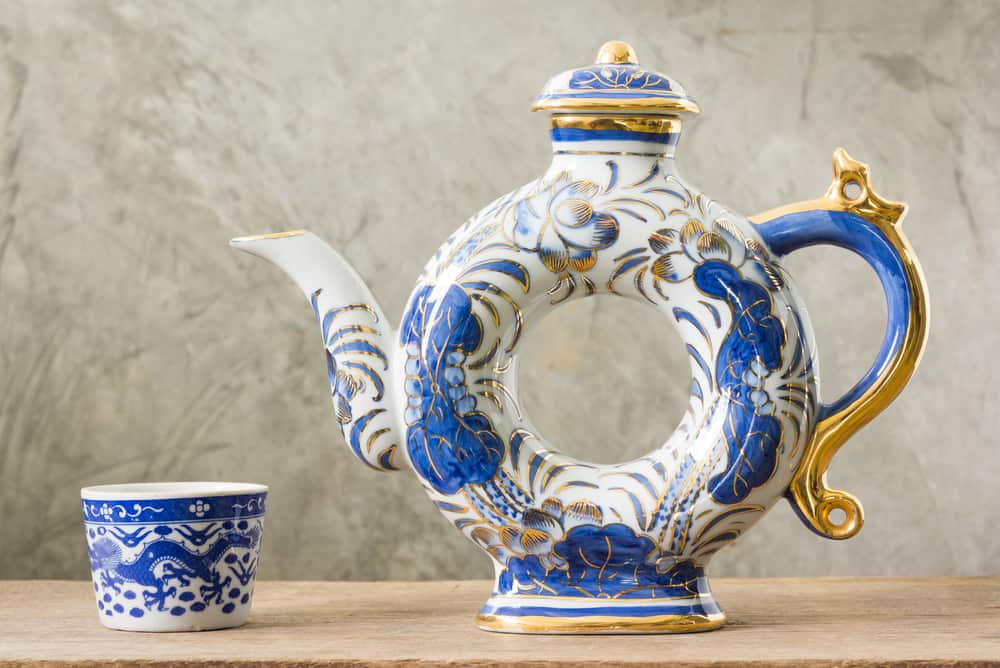 traditional Chinese blue and white ware in teapot and teacup on old wood with cement plaster background