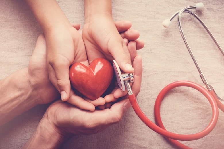 child and adult holding red heart with stethoscope